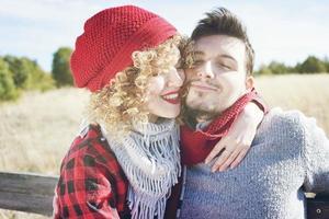 jovem casal romântico de uma linda mulher loira com cabelo encaracolado e usando um boné de lã vermelha, abraços para o namorado e um homem bonito ao ar livre foto