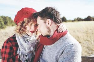 jovem casal de namorados apaixonado se olha apaixonado, sentado em um banco de madeira ao ar livre com a natureza como pano de fundo foto