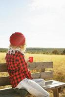 uma jovem mulher por trás com uma camisa xadrez vermelha com um boné de lã e cachecol tomando uma xícara de chá ou café enquanto ela está tomando sol, sentada em um banco de madeira em um campo amarelo com luz de fundo foto