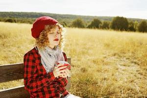 retrato frontal de uma jovem com uma camisa xadrez vermelha com um boné de lã e cachecol tomando uma xícara de chá ou café enquanto ela está se bronzeando, sentada em um banco de madeira em um campo amarelo com luz de fundo do sol de outono foto