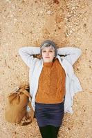 uma jovem mulher caucasiana aventureira deitada no chão arenoso ao lado de uma mochila vestindo um suéter de lã e um boné de lã cinza com o laranja como cor principal foto