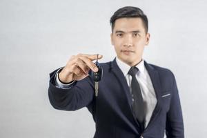 empresário bonito segurando a chave do carro em fundo cinza foto