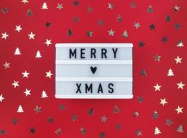 Feliz Natal saudação na caixa de luz e confetes sobre um fundo vermelho. foto