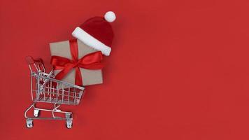 carrinho de supermercado, caixa de presente e chapéu de Papai Noel em um fundo vermelho. foto