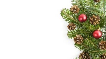 cartão postal de férias com galhos de árvore do abeto, cones e enfeites vermelhos em um fundo branco. banner de Natal com espaço de cópia. foto