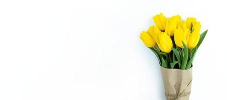 buquê de tulipas amarelas embrulhadas em papel ofício em fundo branco com espaço de cópia. foto