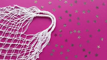 saco de algodão eco de barbante branco sobre fundo rosa com decoração de estrelas de prata. lay flat simples com espaço de cópia. conceito de desperdício zero de ecologia. fotografia de arquivo. foto