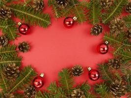 cartão postal de férias com galhos de árvore do abeto, cones e enfeites vermelhos sobre um fundo vermelho. Natal plana deitar-se com espaço de cópia. foto