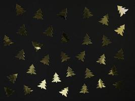 confete da árvore de Natal em um fundo preto. lay plana festiva. foto