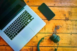 postura plana do laptop, fones de ouvido sem fio e telefone celular na mesa de madeira. foto