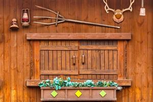 janela de madeira em casa de madeira e decorada com sino e tridente de lâmpada de chifre de planta foto