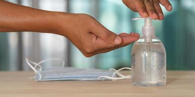 mão com álcool gel desinfetante e máscara médica na mesa foto