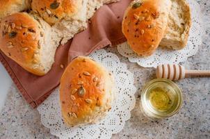pão em uma mesa de trabalho da cozinha. pão caseiro meio amargo com passas, mel e várias sementes. foto