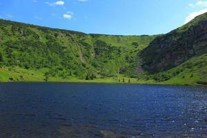 bela vista com lago azul e montanhas verdes foto