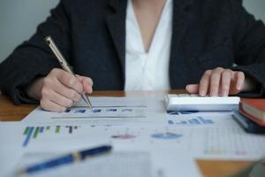 conceito de contabilidade de contador com calculadora de uso feminino e caneta e laptop de computador para trabalhar financeiro e orçamento foto