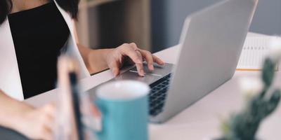 close-up de mãos femininas digitando em um teclado de laptop no escritório doméstico foto
