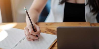 close-up das mãos de uma mulher com computador laptop, caderno e caneta fazendo anotações no escritório de negócios foto