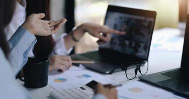 conceito de negócios. empresários discutindo as tabelas e gráficos que mostram os resultados de seu trabalho em equipe bem-sucedido. foto