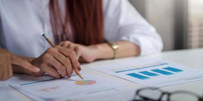 close-up de empresário verificando gráficos financeiros que mostram os resultados de seu trabalho em equipe bem-sucedido no escritório. foto