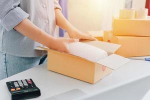 vista do close up da loja online feminina, vendedor do proprietário de uma pequena empresa, pacote de embalagem do empresário, caixa de remessa postal preparando o pacote de entrega sobre a mesa, conceito de negócio autônomo empreendedor foto