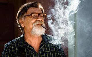 homem de meia-idade com barba grisalha e óculos fuma seu cigarro foto
