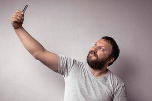 bonito homem barbudo em camiseta cinza olhando para o smartphone foto