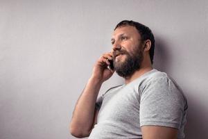 homem barbudo de camiseta cinza segurando um telefone celular foto