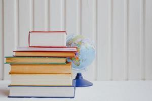 pilhas de livros educacionais e o globo em um fundo branco. conceito de educação. foto