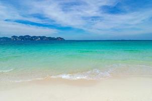 praia branca em um céu azul claro, mar azul foto