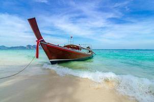 barco de madeira estacionado à beira-mar, praia branca em um céu azul claro, mar azul foto