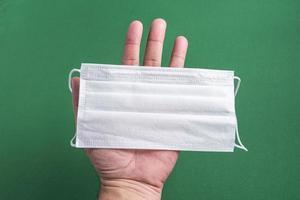 mão de homem segurando máscara cirúrgica foto
