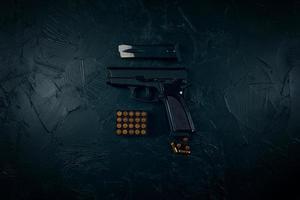 arma com cartuchos na mesa de concreto escuro. foto