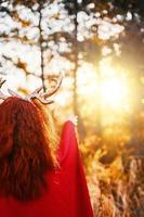 mulher em um vestido longo vermelho com chifres de veado na floresta de outono tentando tocar um pôr do sol foto