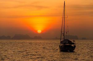 veleiro no mar à luz do sol da noite sobre o fundo de belas montanhas grandes, aventura de verão luxuosa phuket tailândia foto