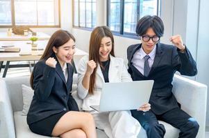 um grupo de 3 empresários fica feliz em frente ao computador. foto