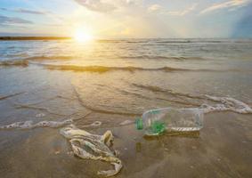 lixo a garrafa de plástico do mar da praia fica na praia e polui o mar e a vida da vida marinha derramado lixo na praia da cidade grande. esvaziar garrafas de plástico sujas usadas foto
