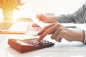 mulher de negócios usando uma calculadora e escrevendo notas. impostos, poupança, finanças e conceito de economia foto