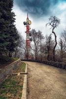 torre de tv ao lado da estrada de asfalto, céu dramático, estrada rural velha da montanha da floresta com cerca de pedra. foto