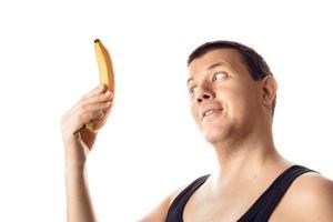 feliz jovem satisfeito olhando para a banana. emoção humana, reação, expressão. isolado no fundo branco. foto