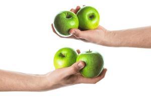homem segurando duas maçãs verdes na mão. isolado no fundo branco. foto