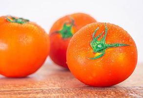 tomates vermelhos maduros com spray de água até a frescura após a colheita em fundo de madeira. foto