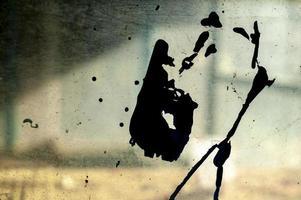 uma forma preta aproximada em um vidro sujo com um fundo interior desfocado abandonado foto