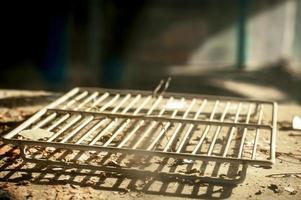 uma velha prateleira de geladeira branca em uma cozinha abandonada e devastada foto