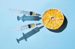 conceito mínimo com uma laranja seca e duas seringas foto