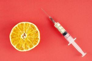 laranja seca e uma seringa com comprimidos amarelos sobre fundo vermelho foto