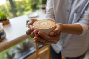 mão de uma mulher segurando uma xícara de café na cafeteria foto