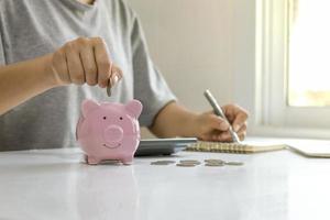 os empresários estão colocando moedas em uma jarra de poupança, incluindo um centavo crescente para ideias de negócios, finanças e contabilidade. foto