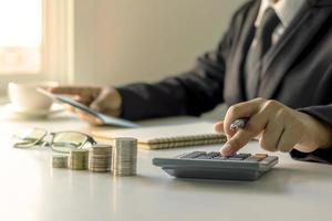 o empresário está segurando uma caneta e pressionando uma calculadora, ideias para planejamento de investimentos e crescimento de dinheiro. foto
