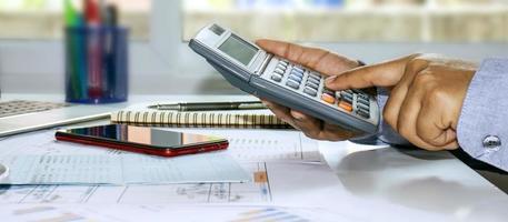 uma foto panorâmica de um homem de negócios pressionando uma calculadora e tomando notas de relatórios contábeis, conceitos de custo e economia de dinheiro.