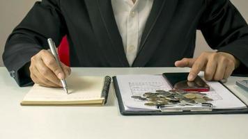 close-up de um homem escrevendo notas financeiras em sua mesa, incluindo documentos financeiros e contábeis. foto